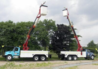 two high reach trucks near trees