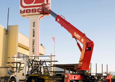 worker installing sign with red m 85 truck