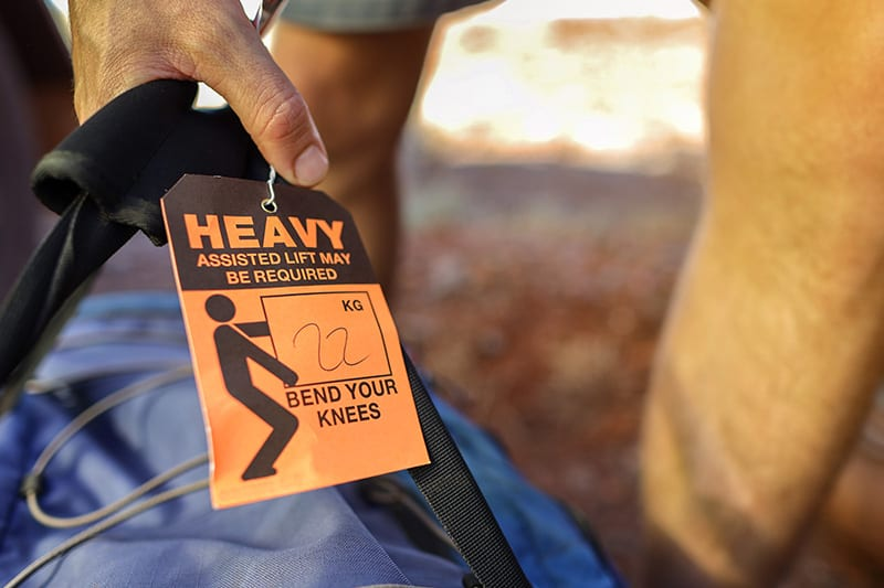 person lifting large back with heavy warning tag